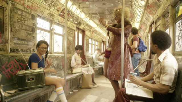 wide angle of interior of subway train cars. passengers or commuters listening to radio and dancing in seats. graffiti covers train car. woman dances in aisle. - 1970 stock videos & royalty-free footage