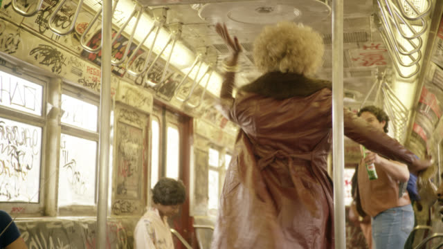 medium angle of interior of subway train cars. passengers and commuters visible. graffiti covers car. woman dances in aisle. - performer stock videos & royalty-free footage