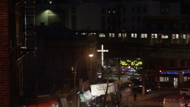 pan up from city streets to train bridge or overpass in urban area or city. church with illuminated cross visible. brick apartment buildings with fire escapes partially visible. el trains visible moving from left to right. pedestrians visible. - religious equipment stock-videos und b-roll-filmmaterial