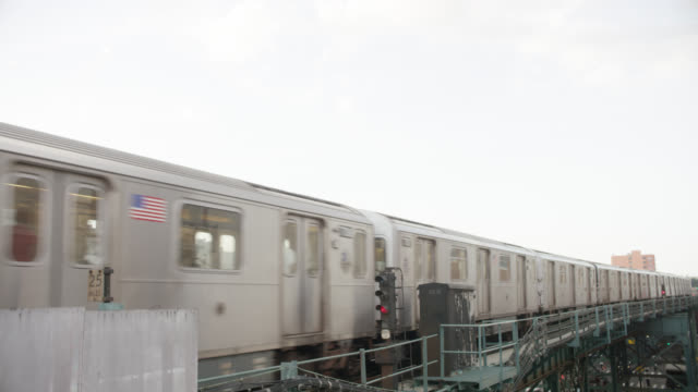 pan up of el train bridge or overpass in city or urban area as train moves by from left to right. multi-story apartment buildings with fire escapes visible in bg. - bronx stock videos and b-roll footage