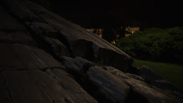 CLOSE ANGLE OF LARGE ROCK, BOULDER, OR STONE IN ST. MARY'S MARK IN THE BRONX. COMMUNITY BUILDING ILLUMINATED AND PARTIALLY VISIBLE IN BG.