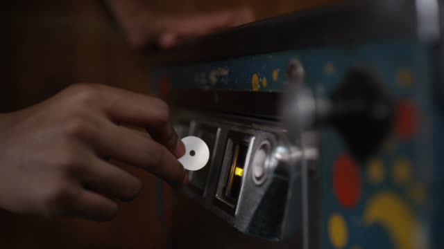 close angle of person putting chip or coin in pinball machine or jukebox. could be arcade. pull lever visible. - pinball machine stock videos & royalty-free footage