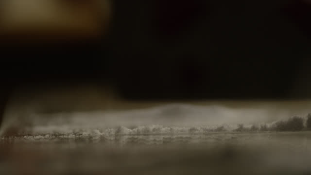 close angle of line of cocaine on table or mirror. hand uses rolled dollar bill to snort cocaine. hand uses playing card to move extra cocaine into new line. - cocaina video stock e b–roll