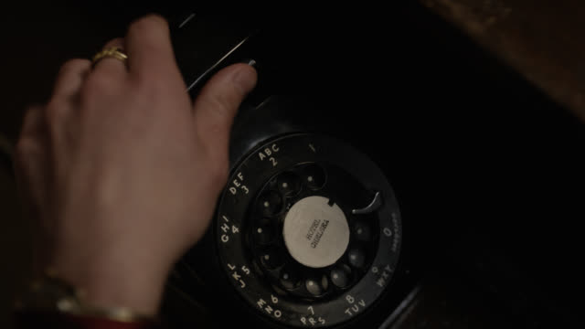 "high angle down close angle of rotary dial telephone. hand picks up receiver and turns dial or wheel. label on phone reads ""hotel chelsea"". could be hotel. - disco combinatore video stock e b–roll"