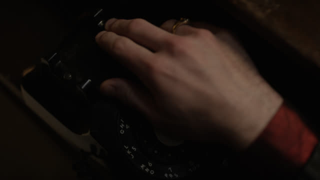 "high angle down close angle of rotary dial telephone. hand picks up receiver and turns dial or wheel. label on phone reads ""hotel chelsea"". could be hotel. - landline phone stock videos & royalty-free footage"