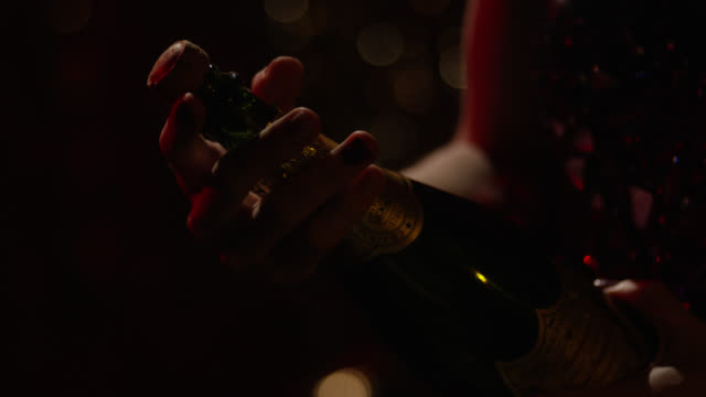 close angle of woman in party or cocktail dress opening bottle of champagne. cork pops off bottle and foam pours out of bottle. could be party or nightclub. - sektkorken stock-videos und b-roll-filmmaterial