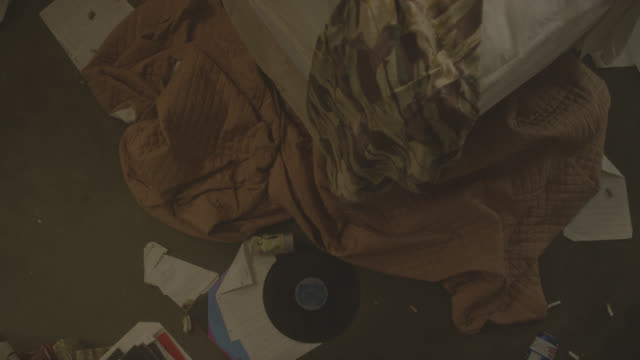high angle down moving pov of messy bedroom with unmade bed. records, sheet music, blankets, beer cans, liquor bottles, partially eaten food, cigarettes, ashtrays, and cassette tapes visible strewn around floor and bed. could be hotel room. - bedroom stock videos & royalty-free footage