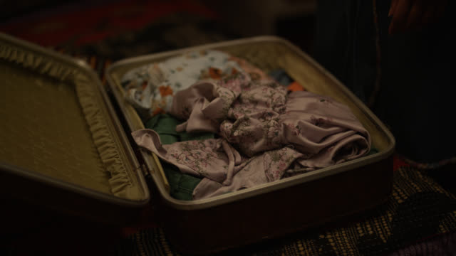 close angle of person closing leather suitcase or overnight case with women's clothes inside. floral blanket or bedspread visible on bed. could be bedroom or hotel room. - bagaglio video stock e b–roll
