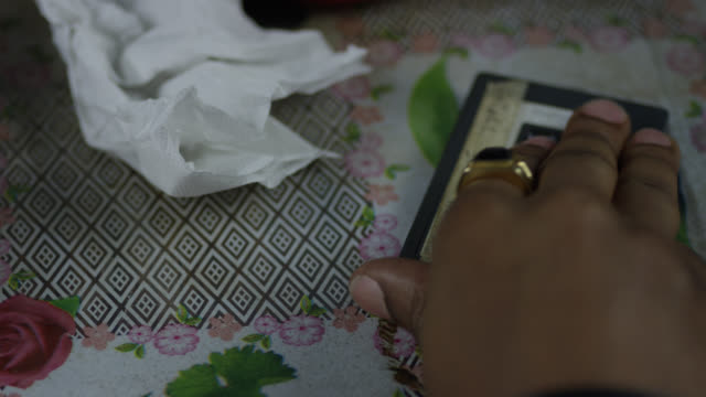 "close angle of hand picking up cassette tape from floral bedspread or tablecloth. crumpled paper towel or napkin visible on bedspread. label on tape reads ""flash live '77 2 of 3"". - crumpled paper stock videos and b-roll footage"