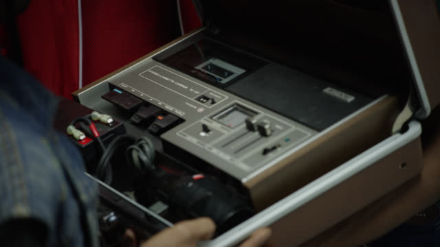 stockvideo's en b-roll-footage met close angle of person in jean jacket opening leather suitcase, briefcase, or carrying case with sony sound equipment inside. could be cassette player or stereo. - attaché