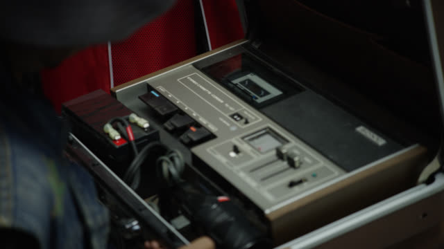 close angle of person in jean jacket opening leather suitcase, briefcase, or carrying case with sony sound equipment inside. could be cassette player or stereo. - aktentasche stock-videos und b-roll-filmmaterial