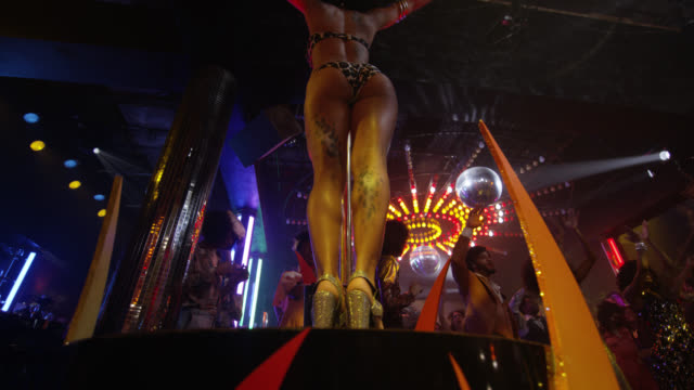 up angle of exotic dancer standing on platform stage in nightclub or disco club. flashing lights on ceiling and disco ball. people visible dancing and clapping. stripper pole visible. - 1970 stock videos & royalty-free footage