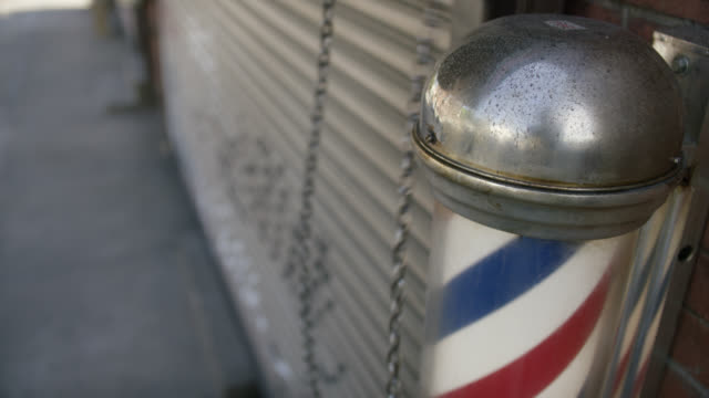 close angle of blue, white, and red barber pole outside barber shop. - beauty salon stock videos & royalty-free footage