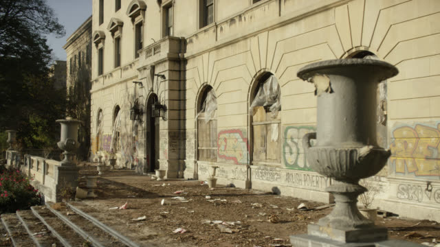 medium angle of abandoned building with graffiti, trash, and garbage visible outside entrance. boarded up windows visible. planters or vases visible atop wall near stairs or steps. could be community center. lower class urban area. - コミュニティセンター点の映像素材/bロール