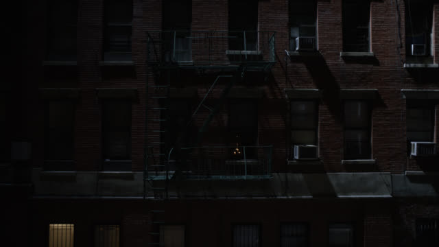 vidéos et rushes de medium angle of brick apartment building with windows, air conditioning units, and fire escapes. candles visible in one window. city or urban area. - 1970