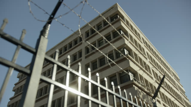 up angle of iron fence or gate topped with barbed wire outside of multi-story building. could be prison, jail, police stations, or police precinct. camera racks focus between fence and building. - prison building stock videos & royalty-free footage