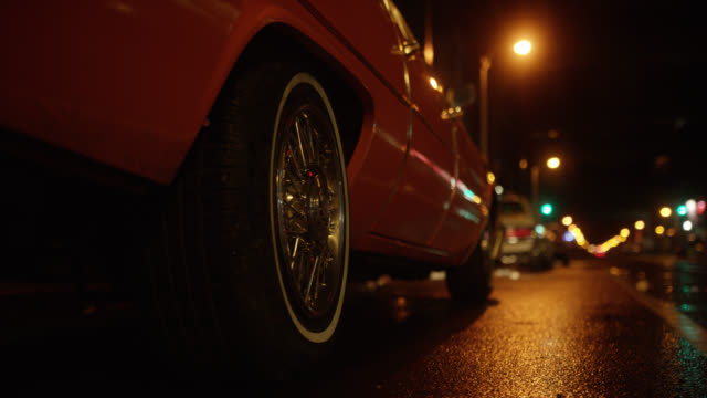 medium angle of white 1974 cadillac coupe deville driving on city street. neon sign for car wash visible in bg. bridge or overpass visible. - キャデラック点の映像素材/bロール