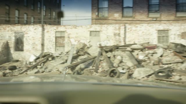 vídeos y material grabado en eventos de stock de medium angle moving pov from inside 1974 cadillac coupe deville on vacant lot. stone, rocks, bricks, trash, garbage, abandoned cars, and graffiti visible. - terrenos a construir