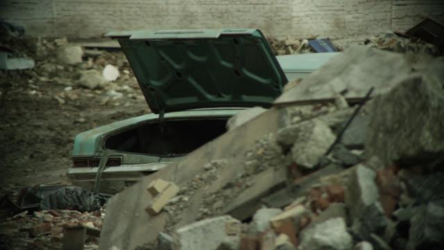 vídeos y material grabado en eventos de stock de medium angle of abandoned car in vacant lot with rocks, stones, garbage bags, and trash. - terrenos a construir