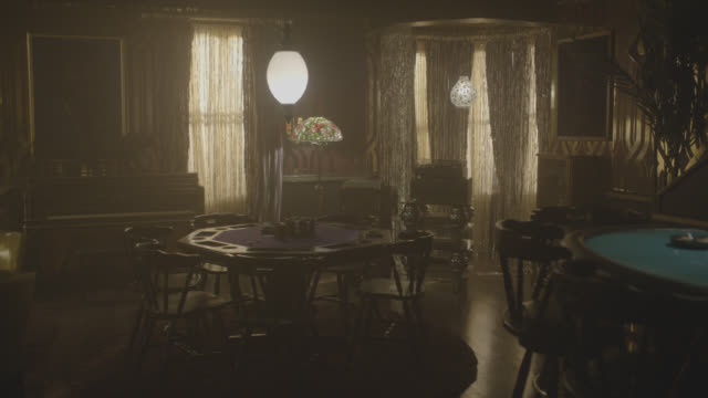 medium angle of gambling parlor. beaded curtain, stained glass lamp, poker table, and blackjack table visible. could be victorian casino. piano visible in bg. camera zooms in to table. safe visible in bg. record player visible in bg. - blackjack video stock e b–roll