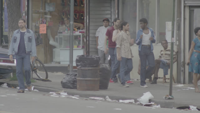 pan left to right of pedestrians walking on sidewalks in lower class urban area. city streets. trash, garbage, cars, and graffiti visible. - 1970 stock videos & royalty-free footage