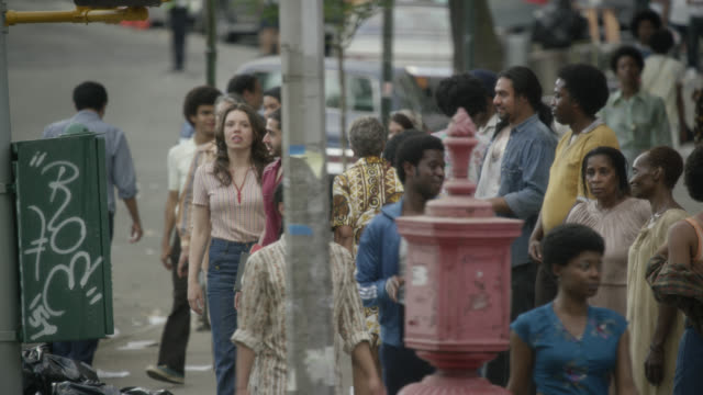 vídeos de stock e filmes b-roll de medium angle of pedestrians walking on sidewalk in urban area. some people stand in line. could be homeless. cars visible on city street. - 1970