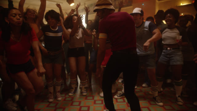 medium angle of people dancing in nightclub, restaurant, hair salon, or at party. people breakdancing while other clap. christmas lights visible. slowed down. - anno 1970 video stock e b–roll