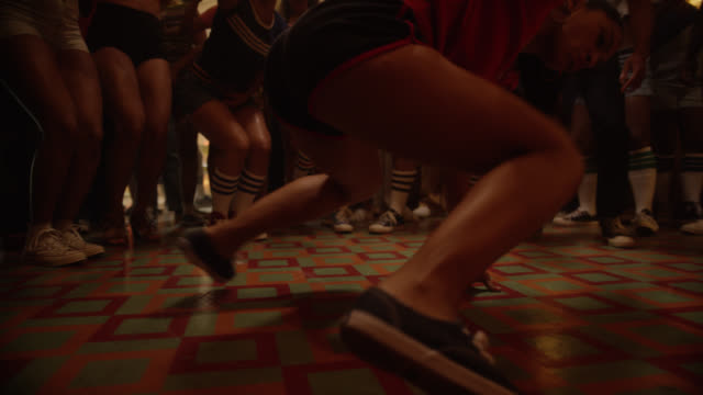 vídeos de stock e filmes b-roll de medium angle of people dancing in nightclub, restaurant, hair salon, or at party. people breakdancing while other clap. christmas lights visible. slowed down. - break dance