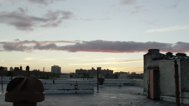 medium angle of rooftop of apartment building in city or urban area. high rise apartment buildings visible in bg. rotating air vent visible in fg. clouds in sky. could be sunset or dusk. - air duct stock videos & royalty-free footage