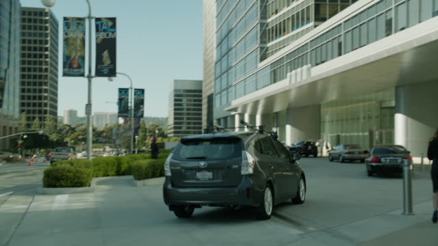 MEDIUM ANGLE OF CARS DRIVING INTO DRIVEWAY OF 2000 AVENUE OF THE STARS IN CENTURY CITY. OFFICE BUILDINGS.