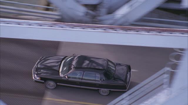 aerial tracking shot of black car crossing drawbridge to left in industrial area. - drawbridge stock videos and b-roll footage