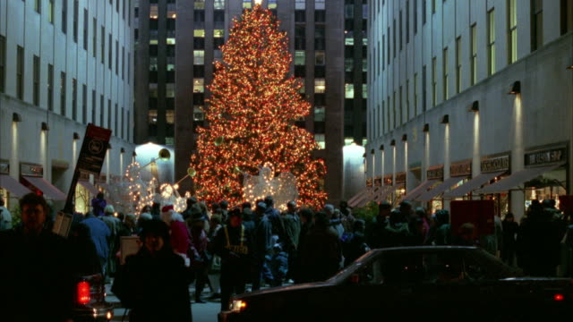 vidéos et rushes de medium angle of giant christmas tree at rockefeller center. see crowd and traffic on streets in foreground passing to left. see police van and city bus. - sapin de noël