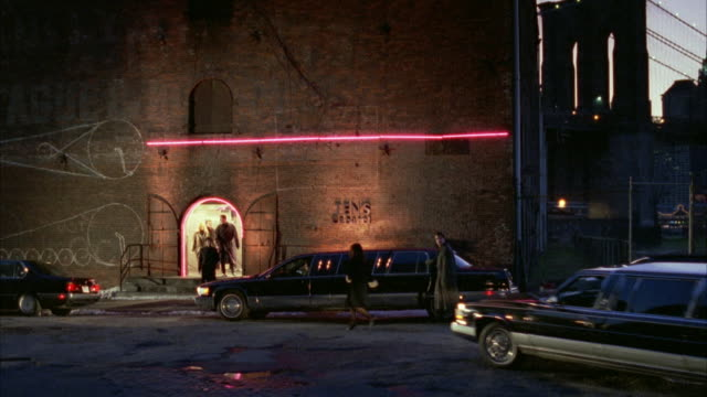 medium angle of parked cars in front of red brick building. see part of brooklyn bridge in right background. limo enters from right and stops in front of entrance of private club. people enter brick building. - 1995 stock videos & royalty-free footage