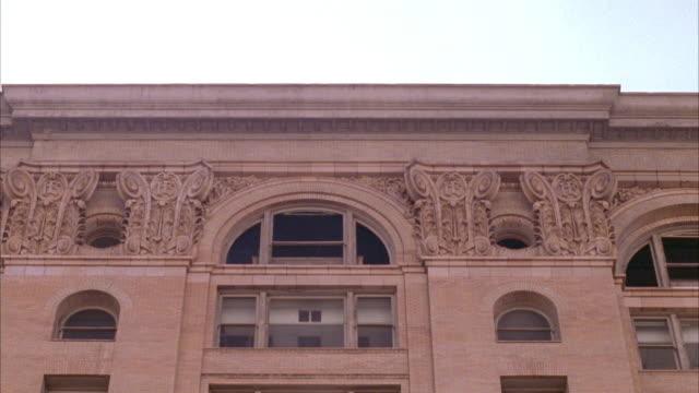 vídeos y material grabado en eventos de stock de medium up angle of tan building with mayan architecture decorated with arched windows on top. could be school of government building. - tan