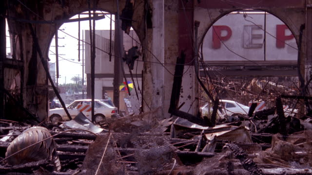 medium angle of destroyed building. rubble visible in foreground. street traffic visible in background through building windows. aftermath of 1992 los angeles riots. - rubble stock videos & royalty-free footage