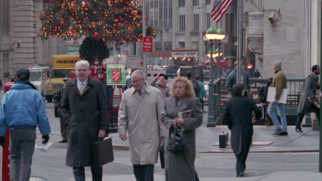 medium angle. new york city street corner during christmas time. christmas tree with lights and salvation army collector visible in background. several pedestrians walk in all directions. white truck and black van enter screen from right and drive across - 1985 stock-videos und b-roll-filmmaterial