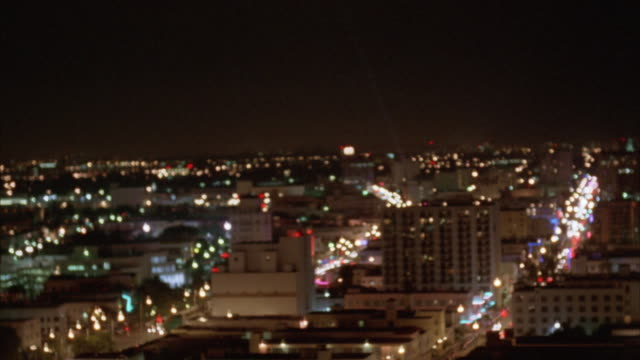 vídeos de stock, filmes e b-roll de aerial circling over shoreline area of downtown miami. pan across several high rises. city lights in background. neon signs glowing, could be nightclubs, bars or restaurants. beachfront visible near end of clip. miami skylines. - 1995