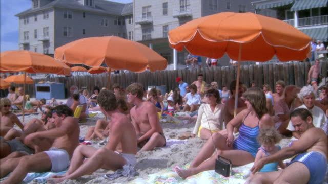 medium angle of beach full of sunbathers and orange beach umbrellas. several beach houses visible in background. - maryland delstat bildbanksvideor och videomaterial från bakom kulisserna