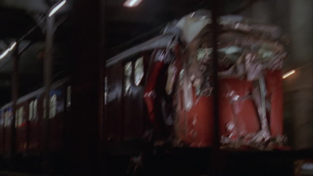 medium angle tracking shot of side of damaged rear of red subway traveling left in tunnel. see support beams in foreground. silver subway follows red subway to left. most likely after crash. - zugunglück stock-videos und b-roll-filmmaterial
