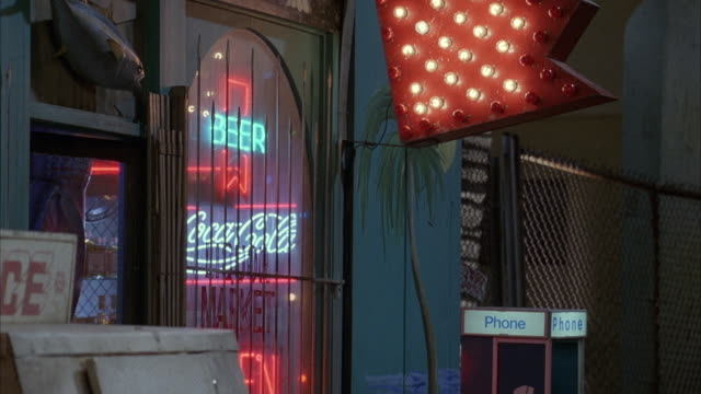 "close angle of storefront of market or liquor store. red neon sign shaped in arrow points toward door. neon sign of ""beer"" and ""coca cola"" seen through gate and glass door. public telephone on right, man passes by to right. - liquor store stock videos and b-roll footage"