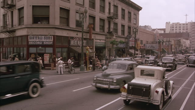 medium angle of street corner in downtown los angeles marketplace. see vintage cars pass by in front to left. - 1948年点の映像素材/bロール