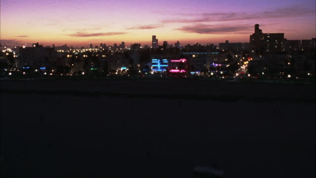 vídeos de stock, filmes e b-roll de aerial fast forward moving pov of ocean by miami skyline. sky has tint of red and purple. beauty shot. - 1995