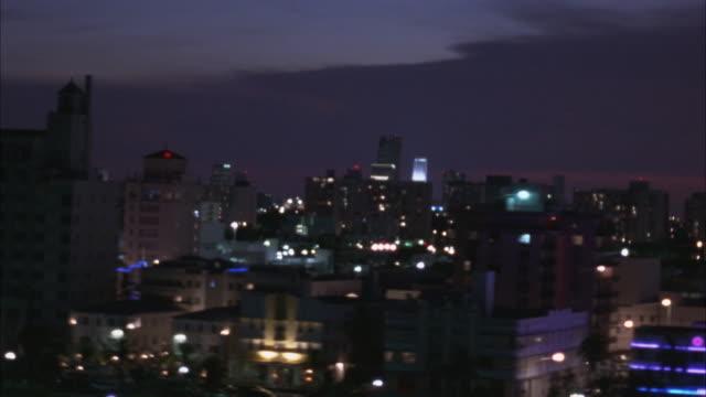 vídeos de stock, filmes e b-roll de aerial side moving pov along pier, see miami skyline in far background. beauty shot. - 1995