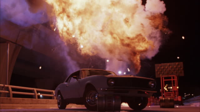 medium angle of gray vintage car of ford mustang parked on freeway ramp. see yellow lit arrow. car explodes, ball of fire, flames and smoke billow out of windows. explosions. - 1995 stock videos & royalty-free footage