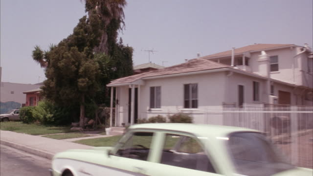stockvideo's en b-roll-footage met medium angle 3/4 side drive pov passenger's side of residential area in south central los angeles. pass by row of house and parked cars by sidewalk. - 1993