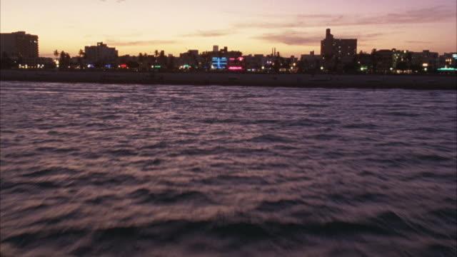 vídeos de stock, filmes e b-roll de aerial fast forward moving pov of ocean and pier. miami skyline in far background. sky has tint of purple and orange. beauty shot. - 1995