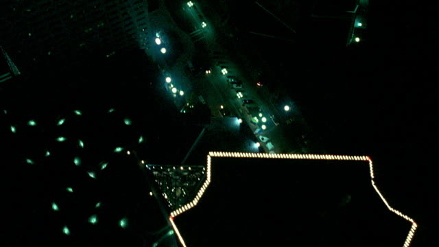 aerial birdseye pov of downtown miami skyline. see rooftops of hotel intercontinental building, then past other high rise office buildings. passes building with many red neon lights. - other stock videos and b-roll footage