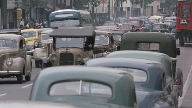 vídeos de stock e filmes b-roll de medium angle of downtown city street with classic cars and trolley. pedestrians walk on street and cars stopped in traffic. - 1948