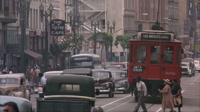 """pan right to left of downtown city street with classic cars and trolley. movie marquee reads """"oscar micheaux's 'the betrayal.'"""" see old stoplight with street sign that reads """"34th st. 1100 e."""" policeman stands directing traffic in intersection. - 1940~1949年点の映像素材/bロール"""