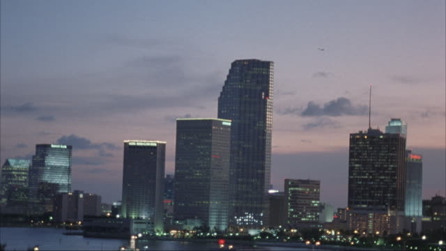 vídeos de stock, filmes e b-roll de wide angle moving pov from car of downtown miami skyline and waterfront. see several high rise office buildings and one tall white office building. - 1995